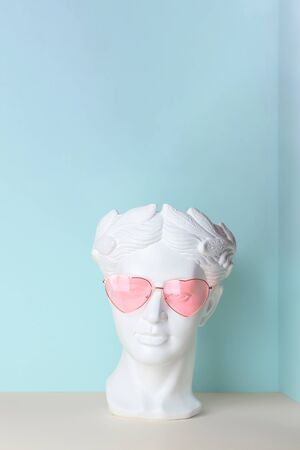 White sculpture of an antique head in pink glasses with hearts. On a geometric background of two colors