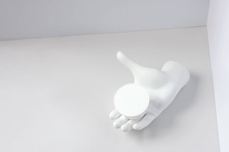 White composition with a jar of cream on the plaster hand in the corner. Concept on the theme of youthful skin.