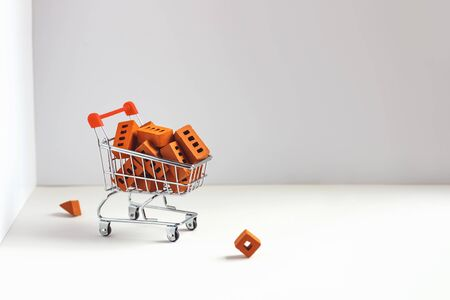 Lots of orange bricks in the shopping trolley. Concept on construction or self-isolation