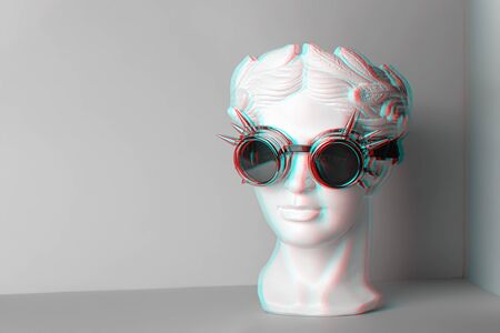 White sculpture of an antique head in rock glasses. On a geometric background of two colors.