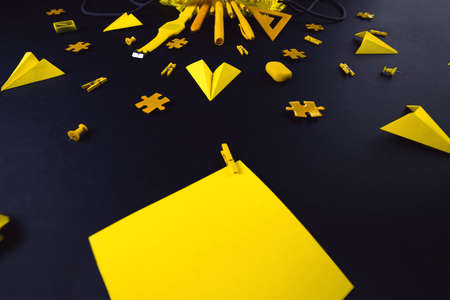 A concept on the subject back to school. The students yellow stationery on a black background