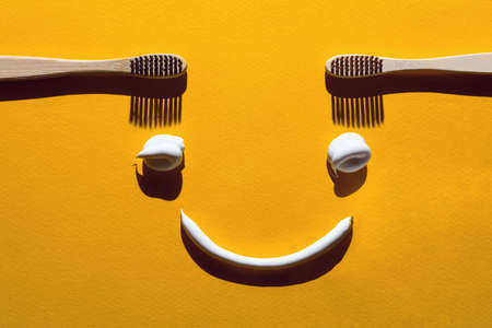 Wooden toothbrushes and pasta on a yellow background. Dental concept in the form of a funny face
