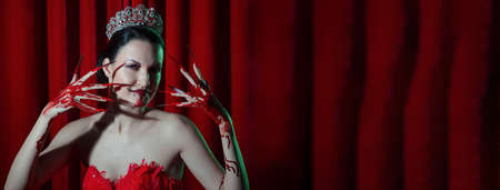 A woman vamp in a red dress, a crown with a bright manicure and blood. An image of Halloween Stockfoto