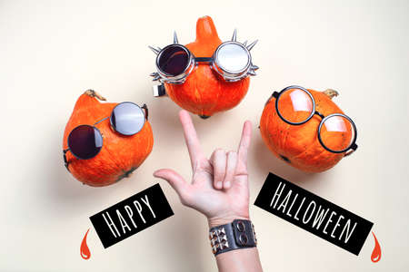 Three orange rocker pumpkins with glasses and a mustache on a light background. Halloween concept.