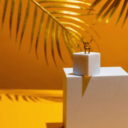 A small figure of a golden deer - a symbol of the new year on two white squares, in the style of monumentalism, on a yellow background, behind the leaves of a palm tree.