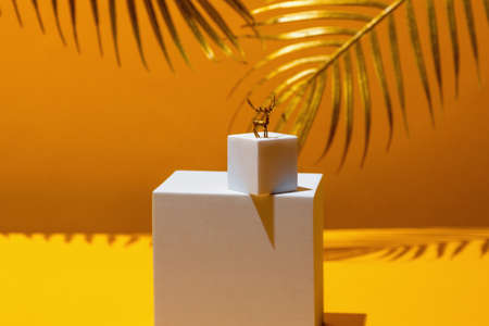 A small figure of a golden deer - a symbol of the new year on two white squares, in the style of monumentalism, on a yellow background, behind the leaves of a palm tree