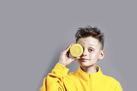 a boy in a bright yellow jacket with a lemon in his hand on a blue background