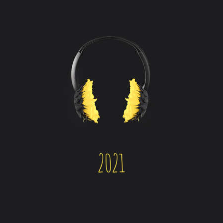 Headphones with yellow sunflowers hover in the air on a gray background, color concept of the year 2021