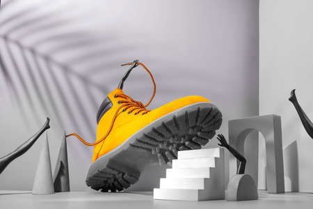 Shoe concept, yellow boots on the stairs, women's legs and hands, palm shade on gray background, arch and other geometric shapes, color 2021