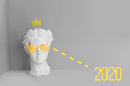 White sculpture of an antique head in glasses with hearts. On a geometric background yellow and gray color