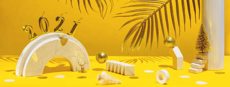 Golden candles with the new year 2021 on the marble arch, palm leaves, column, stairs, balls, Christmas trees, confetti on a yellow background with the horizon. Festive trend still life.