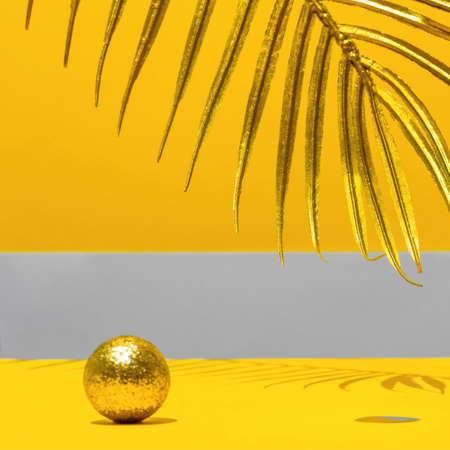 Golden candles with the new year on the marble arch, palm leaves, confetti on a yellow background with the horizon. Festive trend still life. Color 2021