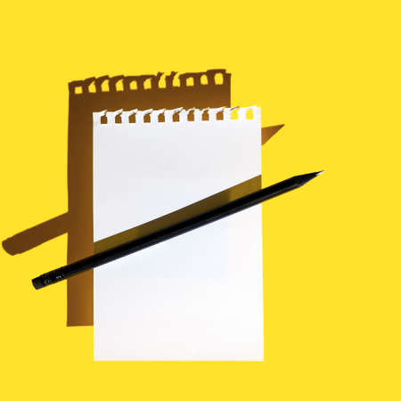 a blank sheet of Notepad, black pencil and hard shadows on a bright yellow background
