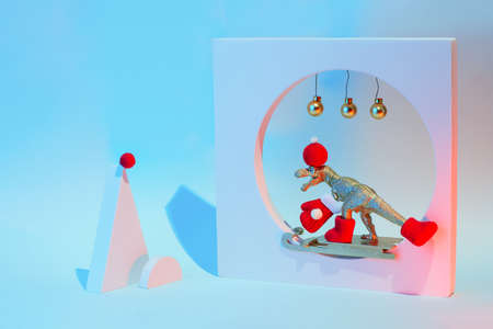 New Year and Christmas concept with a dinosaur on a sled with geometric shapes, in a neon light. 스톡 콘텐츠