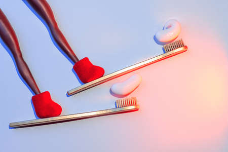 Winter dental concept with toothbrushes and toothpaste in the form of skis with red felt boots riding from the mountain