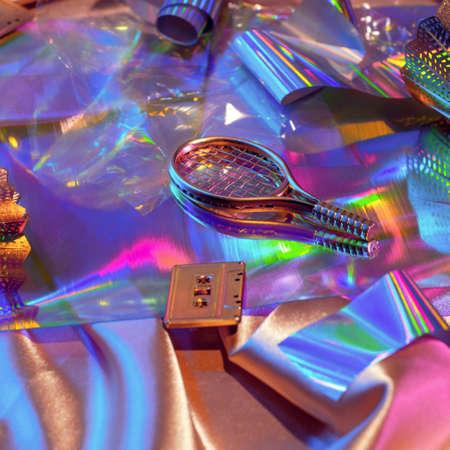 Holographic rainbow iridescent fabrics surface and objects from the 90s shuttlecock, racket, audiocassette, 80s retrospective, sports concept.
