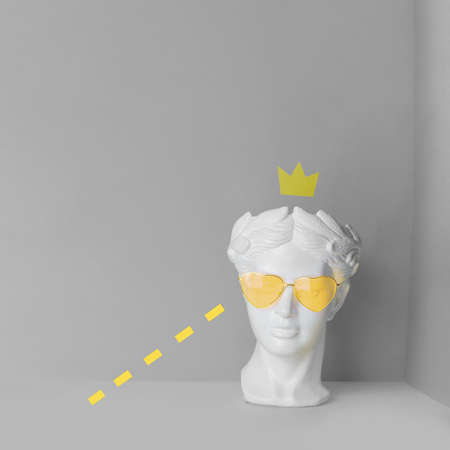White sculpture of an antique head in yellow glasses with hearts. On a geometric background of two colors.