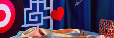 Small golden cupid marks his target with an arrow at the heart, valentines day concept.