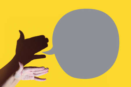 shadow theater. hand shows dog with open a mouth. Shes talking on yellow background