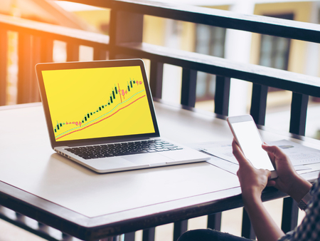 woman holding smart phone and trading stock on laptop,investment concept