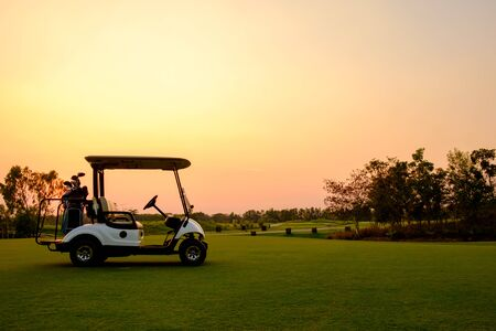 Golf cart car in fairway of golf course with fresh green grass field and cloud sky and tree  on sunset time Reklamní fotografie - 135406156