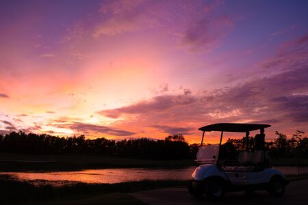 silhouette golf cart in golf course with colorful twilight sky soft cloud for background backdrop use Reklamní fotografie - 136857876
