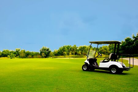 Golf cart car in fairway of golf course with fresh green grass field and cloud blue sky and tree