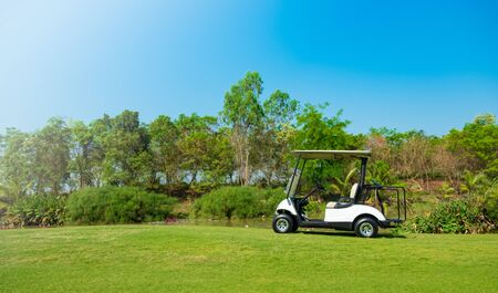 Golf cart car in fairway of golf course with fresh green grass field and cloud sky and tree Reklamní fotografie - 136857951
