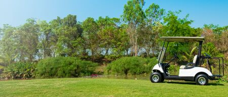 Golf cart car in fairway of golf course with fresh green grass field and cloud sky and tree Reklamní fotografie