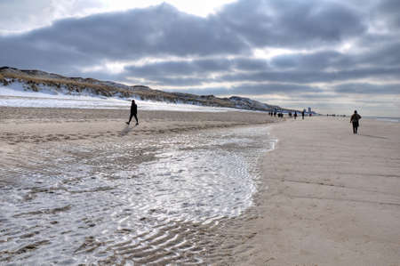 german north sea region: Walk on the beach on Sylt with backlight and dark clouds