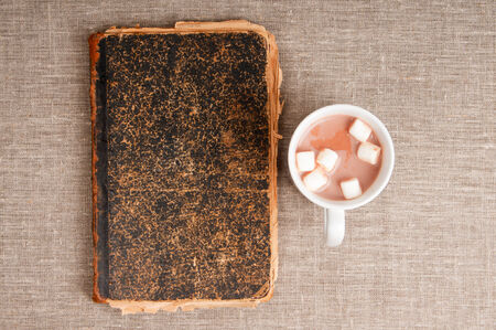 Cup of coffee with marshmallows around an old book on a linen background photo