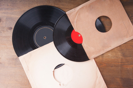 Vintage vinyl records in an envelope on a wooden table photo