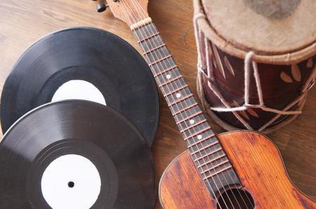 Vintage akoestische gitaar, drum en vinyl record op een houten achtergrond