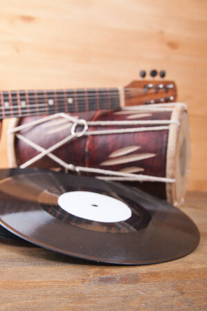 darbuka: Vintage acoustic guitar, drum and vinyl record on a wooden