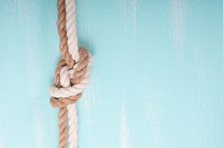 Marine rope with a knot on a wooden background turquoise photo