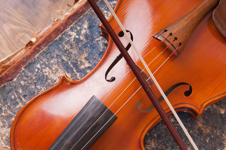Violin, bow and old book table Standard-Bild