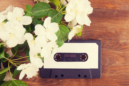 Audio cassette and spring flowers on a wooden table photo