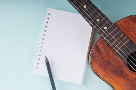 Beetje gitaar en lege notebook met potlood op de azuurblauwe oppervlak