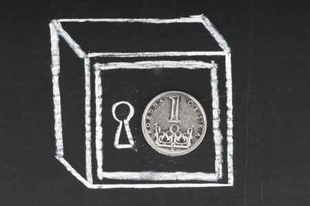 koruna: Czech koruna coin and drawn on a chalkboard safe. Save money concept.