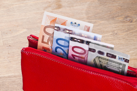 Open red wallet with euro banknotes on wooden background Archivio Fotografico
