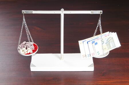 medical preparation: drugs and pills and money on the scales Stock Photo
