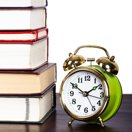 Time to learn. Books and alarm clock on the table photo
