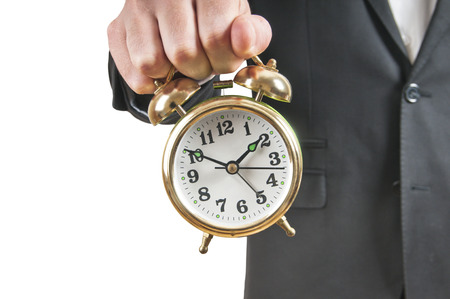 Businessman holding alarm clock photo