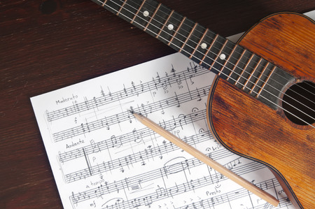 Music notes, vintage guitar and two pencils on table