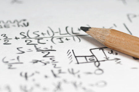 紙のシートを背景として原子力の計算と量子物理学でいっぱい