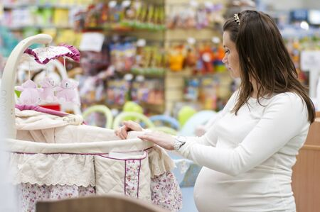 woman hanging toy: pregnant woman choosing cot for baby