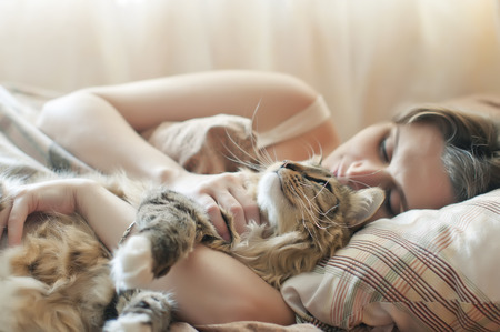 girl sleeping in bed with her cat