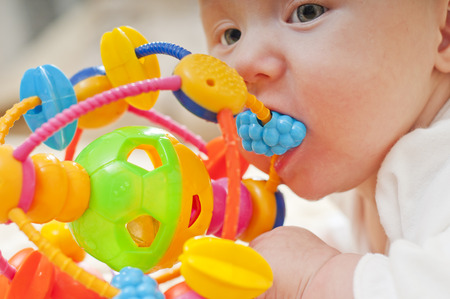 teether: Little baby chewing a toy