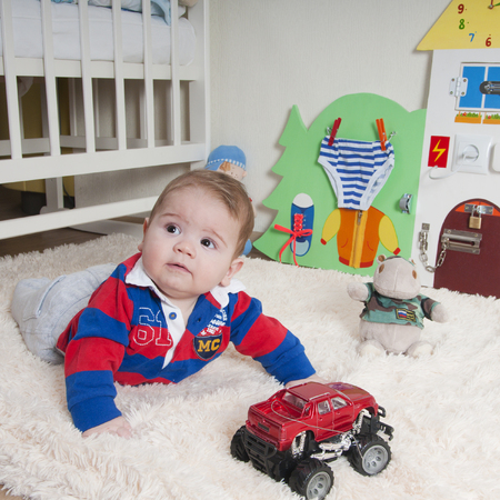 enfant qui joue: Baby boy joue sur le tapis à la maison ou dans le jardin d'enfants