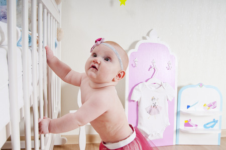 babyboy: Little baby girl ( 7 mounth old ) standing at childrens room near the bed